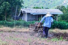 De Thaise landbouwer die het lopen tractoren voor gecultiveerde grond met behulp van voor bereidt aanplanting voor Stock Afbeelding
