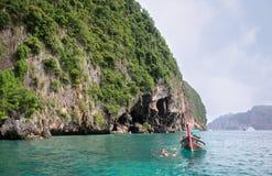 De Thaise lange staartboot en de niet geïdentificeerde toeristen snorkelen dichtbij de ingang in Viking Cave van Phi Phi Ley Isla stock afbeeldingen