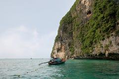 De Thaise lange staartboot en de niet geïdentificeerde toeristen snorkelen dichtbij de ingang in Viking Cave van Phi Phi Ley Isla royalty-vrije stock fotografie