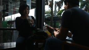 De Thaise man en de vrouw zitten ontspannen en sprekend met het drinken van ijskoffie in koffiewinkel stock video