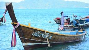 De Thaise mens inspecteert en herstelt het houten visserijboot drijven stock videobeelden