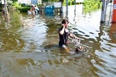De Thaise mensen berijden een fiets, de Overstroming van Bangkok Stock Foto