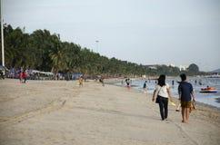 De Thaise mensen en de minnaars die op het strand met wind lopen en golven a Stock Afbeelding