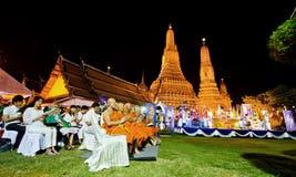 De Thaise mensen en de monnik sluiten zich aan bij moraal bidden aftelprocedure in de temperaturen van Wat Arun Stock Foto's