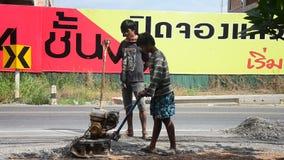 De Thaise mensen gebruiken grondpersen in bouwwerf het werken en reparatieoppervlakte van weg bij landelijke wegen stock video