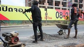 De Thaise mensen gebruiken grondpersen in bouwwerf het werken en reparatieoppervlakte van weg bij landelijke wegen stock videobeelden