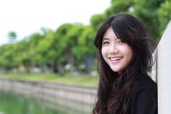 De Thaise mooie het meisjes Zwarte Kleding van de studententiener ontspant en glimlacht royalty-vrije stock afbeeldingen