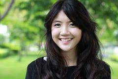 De Thaise mooie het meisjes Zwarte Kleding van de studententiener ontspant en glimlacht Stock Foto's