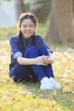 De Thaise 12s zitting van het jarenmeisje op tuingebied toothy het glimlachen gezicht stock afbeeldingen