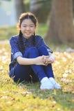 De Thaise 12s zitting van het jarenmeisje op tuingebied toothy het glimlachen gezicht stock foto's