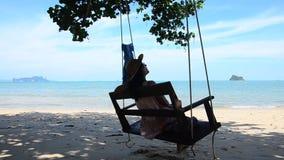 De Thaise vrouw zit en ontspant op houten bankschommeling bij het strand stock videobeelden