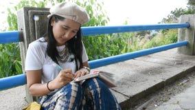 De Thaise vrouw zit en schrijft nota over het boek voor geheugen van detail tussen reis stock videobeelden