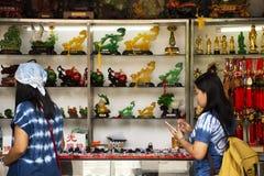 De Thaise vrouwen selecteren en kopen heilige amulet en jade bijkomende de herinneringswinkel van vormamuletten van Kaiyuan-Tempe stock afbeelding