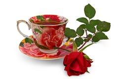 De thee in een kop met nam toe Stock Afbeeldingen