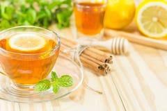 De thee met de kaneel van de munthoning en citroen op houten achtergrond, warm t Stock Foto