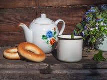 De thee met ongezuurde broodjes en een klein boeket van bloemen in een blauw overvallen op een rustieke portiek stock afbeeldingen