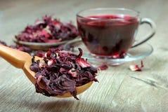 De thee van de hibiscus Hibiscusthee in een houten lepel op een achtergrond van een kop van verse thee Vitaminethee voor koude en royalty-vrije stock afbeeldingen