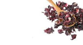 De thee van de hibiscus Hibiscusthee in een houten lepel op witte achtergrond Vitaminethee voor koude en griep stock afbeeldingen