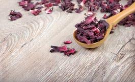 De thee van de hibiscus Hibiscusthee in een houten lepel Vitaminethee voor koude en griep royalty-vrije stock afbeelding