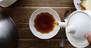 De thee van de ketel giet langzaam in porseleinkop stock video