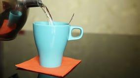 De thee wordt gegoten in een blauw ceramisch glas stock video