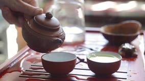 De theeceremonie De vrouw giet thee in een theekom stock footage