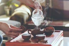 De theeceremonie De vrouw giet warm water in de theepot stock fotografie