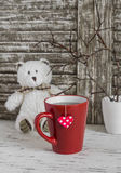 De theekop met een eigengemaakt theezakje met document harten en het stuk speelgoed dragen op een lichte rustieke houten achtergr Stock Fotografie