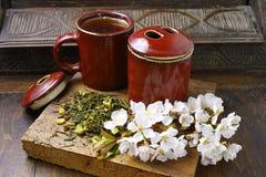 De theekoppen van Japan met groene thee en sakurabloemen Stock Afbeelding