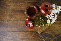 De theekoppen van Japan met groene thee en sakurabloemen Stock Foto's