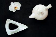 De theepot en de uitstekende witte ceramische kop met thee op donkere achtergrond met orchidee bloeien, kopiëren ruimte, close-up stock foto
