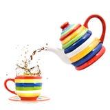De theepot van de kleur met kop en plons van thee Stock Fotografie