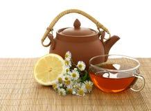 De theepot van de kop thee, van de kamille en van de klei Stock Afbeeldingen