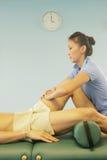 De therapeut die van de massage een massage geeft Stock Foto's