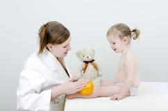 De therapeut maakt een kindmassage Stock Foto