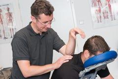 De therapeut van de sportenmassage op het werk Stock Afbeelding