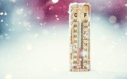 De thermometer op sneeuw toont lage temperaturen in Celsius of farenheit stock foto's