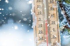 De thermometer op sneeuw toont lage temperaturen in Celsius of farenheit stock foto