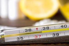 De thermometer van het glaskwik met op hoge temperatuur van 37 5 tegen de achtergrond van geneesmiddelen, citroen, thee, volksrem Stock Foto