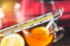De thermometer van het glaskwik met op hoge temperatuur van 37 5 tegen de achtergrond van geneesmiddelen, citroen, thee, volksrem Royalty-vrije Stock Foto's
