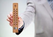 De thermometerlezing van de zakenmanholding op hoge temperatuur Royalty-vrije Stock Foto's