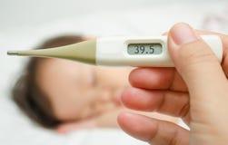 De thermometervoorgrond van de moederholding en ziek meisje in bed royalty-vrije stock fotografie