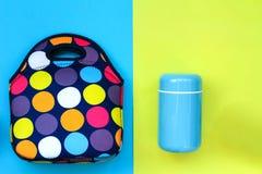 De thermosflessen van zachte blauwe kleur en een lunchdoos doen op een geel-blauwe achtergrond in zakken stock afbeeldingen