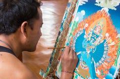 De Tibetaanse kunstenaar creeert het traditionele Thangka-schilderen stock foto
