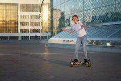 De tiener berijdt een gyroscooter, met een glimlach en positieve emoties stock foto's