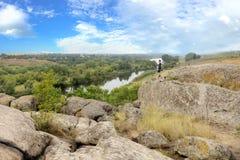 De tiener bevindt zich bovenop een grote steenkei op de bank van de Zuidelijke Insectenrivier en bekijkt de hieronder rivier Stock Foto
