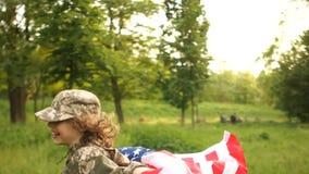 De tiener in camouflage eenvormig met ons markeert op een picknick om Onafhankelijkheidsdag te vieren stock videobeelden
