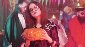 De tiener danst in langzame motie met een gesneden pompoen in haar hand bij een Halloween-partij stock video