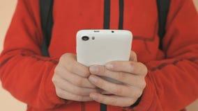 De tiener die een witte mobiele telefoon binnen houden stock videobeelden
