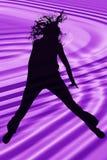 De Tiener die van het silhouet over Purple springt Stock Foto's